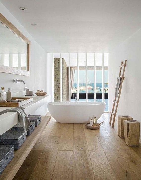 tolle badideen mit holzfußboden, badewanne vor trennwand aus weißen holzlamellen mit blick aufs wohnzimmer und meer, waschtisch mit holzregal, spiegel im holzrahmen