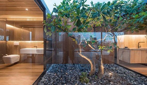 minimalistisches-haus-mit-holzinterior-und-hofgarten-mit-baum-und-bodenbeleuchtung-zwischen-bad-und-küche