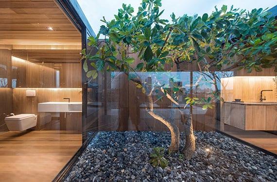 kleiner hofgarten mit baum in kiesboden als natürliche raumtrennung und mittelpunkt des innenraumes