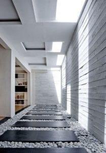 minimalistisches-interieur-design-mit-betonwand,-kieselsteinboden-mit-steinplatten-und-oberlichter