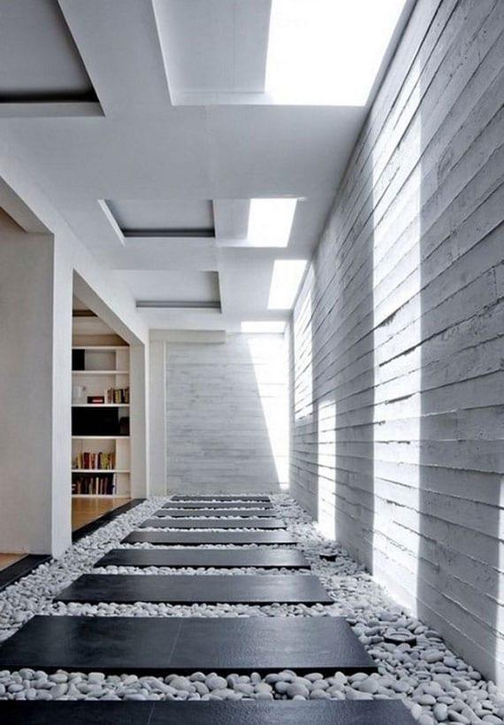 moderne gestaltungsideen für wohnzimmer mit offenem grundriß, oberlichter über korridor mit sichtbetonwänden und grauem kieselboden mit schwarzen steinplatten