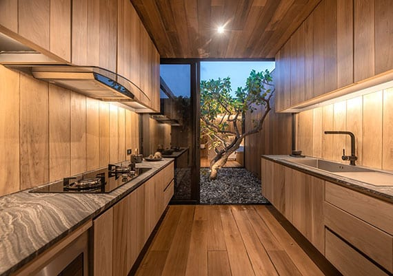 attraktive küchengestaltung in holzoptik mit gegenseitigen küchenarbeitsplatten und glastür zum außenbereich