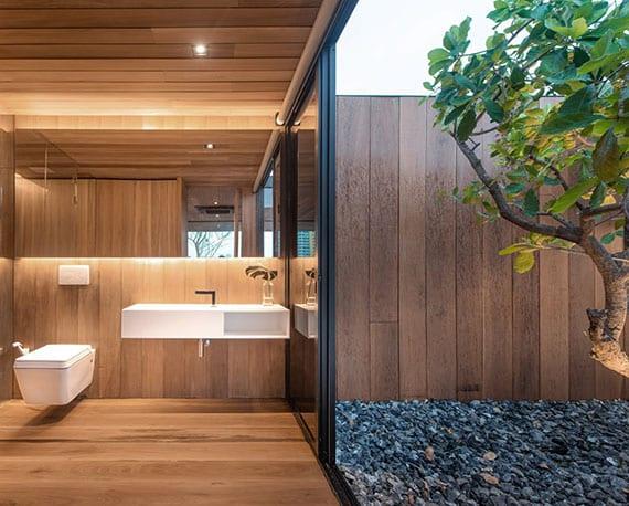 stilvolle badgestaltung in holzoptik mit modernem waschtisch und wand-wc in weiß, indirekt beleuchtetem badspiegel und glastür zum steingarten