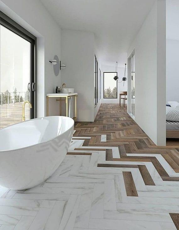 minimalistisches bad mit attraktiver bodengestaltung aus fischgrätparkett und weiße marmorfliesen, freistehender badewanne und glasschiebetür zur terrasse