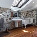 mediterranes bad interieur design mit massivholzboden,mauerwand mit waschbecken und weißem schrank im retro stil, ganzkörperspiegel im schwarzen metallrahmen, dachfenster mit jalousien