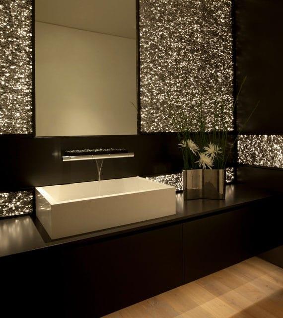 modernes lichtkonzept fürs bad mit led beleuchtung hinter perforierten Alu-Wandpaneelen_elegantes bad design in schwarz mit holzfußboden, rechteckigem aufsatzwaschbecken und moderner waschtisch-wandbaterie