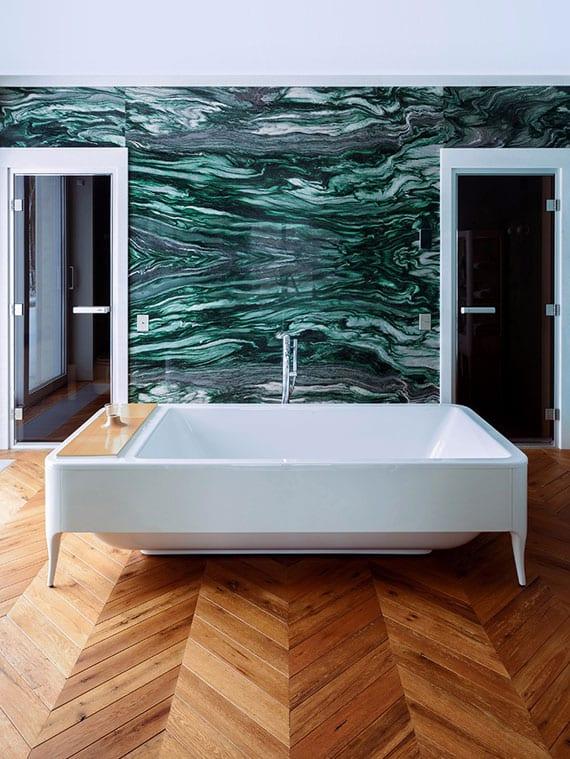 modernes bad mit holzfußboden in fischgrätband, akzentwand mit natursteinverkleidung, opalglastüren und designer badewanne rechteckig