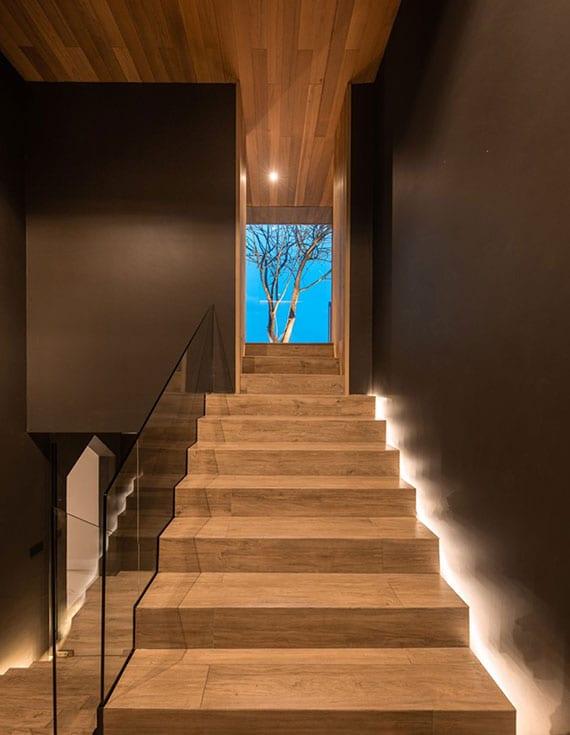 attraktive gestaltungsidee für innentreppe mit holztrittstufen, glasgeländer, indirekter bodenbeleuchtung und wandfarbe braun