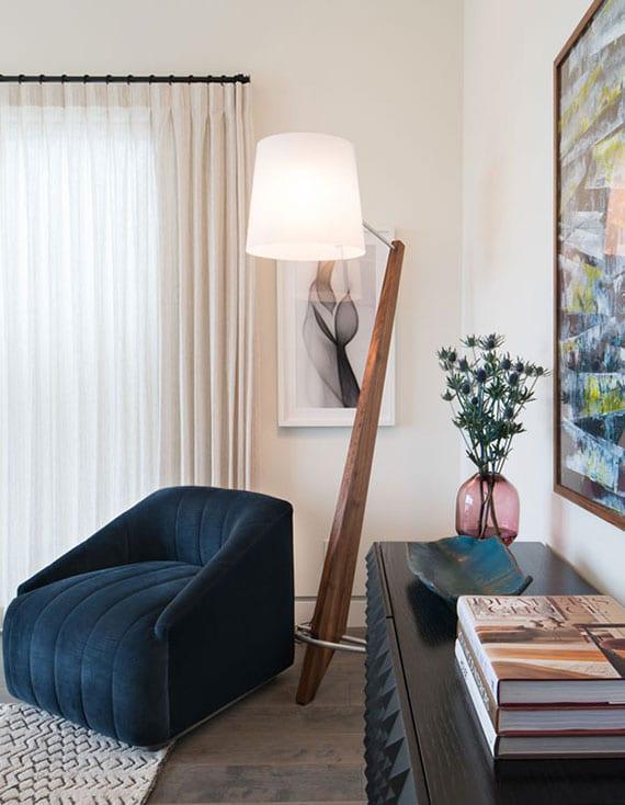 stilvoll eingerichtetes wohnzimmer mit designer stehlampe aus holz, polstersessel blau und attraktiven sideboard aus holz mit 3d schranktürdesign