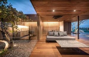 wohnen-auf-dem-dach_ein-traumhaus-mit-schlichtem-und-modernem-interior-design-in-holzoptik-und-transparente-raumtrennung-durch-innenhofgarten-hinter-verglasung