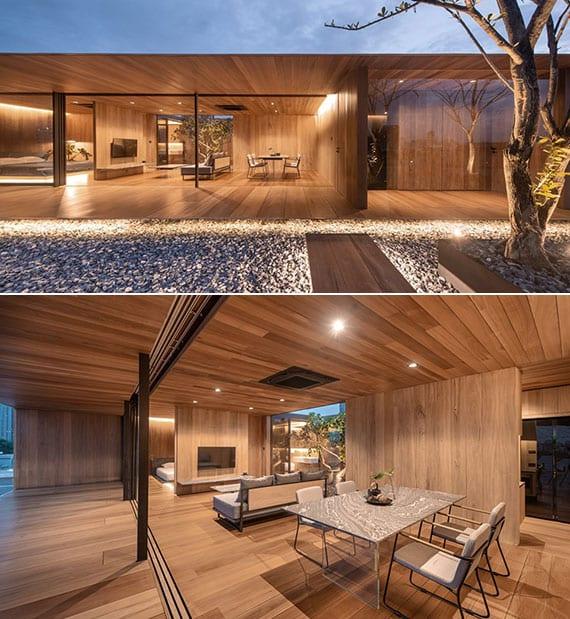 inspiration für stilvolle wohnzimmergestaltung mit holz interior design, essbereich mit designer-esstisch aus naturstein und weißen esszimmerstühlen, große glasschiebetür zur überdachten holzterrasse