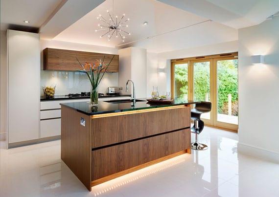lichtgestaltung moderner küche in weiß und holzoptik mit akzentlicht aus led-streifen, wandlampen und einbaudeckenleuchten