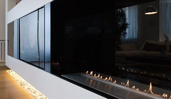 zeitgenössisches-wohnzimmer-interieur-design-mit-kies-unter-moderner-tv-wand-mit-einbaukamin-und-indirekter-beleuchtung