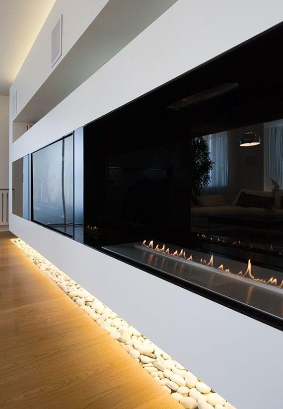 indirekt beleuchtete lose kieselsteine als dekoration im wohnzimmer mit parkettbodenbelag, bioethanol kamin und einbau-fernseher