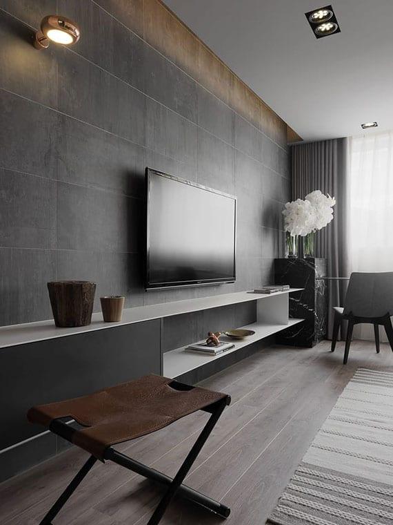 modernes wohnzimmer interieur in dunkelgrau, weiß und holz mit TV-Lowboard, wandverkleidung mit natursteinfliesen, indirekter beleuchtung