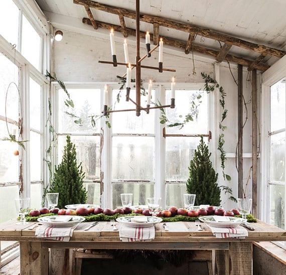 traumhafte winterdekoration im rustikalen stil mit natürlichen girlanden aus Grün, diy kronleuchter mit kerzen und tischdeko mit roten äpfeln und moos