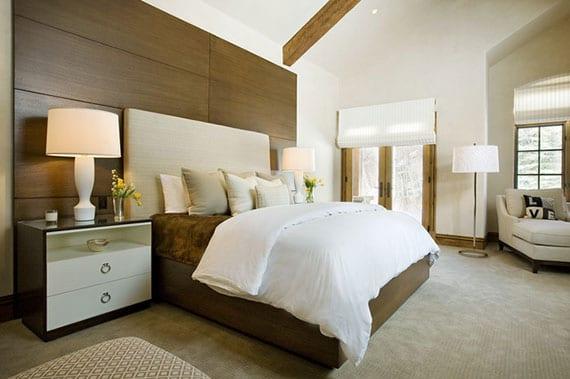 schlafzimmer modern und wohnlich einrichten mit luxus-boxspringbett und modernen nachttischen mit weißen tischlampen vor akzentwand aus holz, teppichboden in beige und liegesofa mit stehlampe vor sprossenfenster