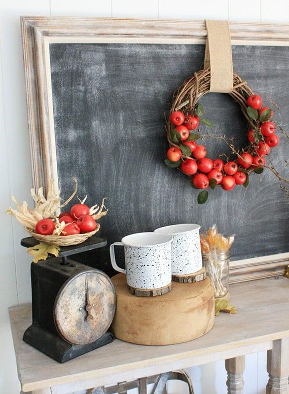 herbstdeko im vintage stil mit diy apfel-kranz an Schwarztafel im Bilderrahmen, weißen kaffeetassen aug holzscheibe und alter waage mit roten äpfeln