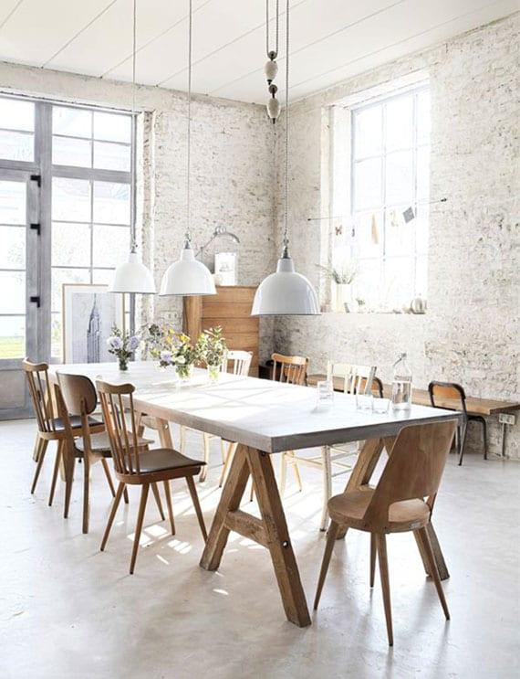 esszimmer design im rustikalem wohnstil mit nachten ziegelwänden, vintage-pendellampen weiß und holzesstisch mit unterschiedlichen esszimmerstühlen aus holz