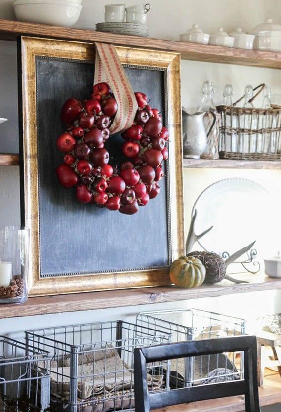 coole bastelidee für originelle DIY wanddeko mit schwarzer kreidetafel in bildrrahmen und kranz aus roten äpfeln