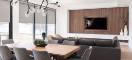 minimalistisches wohnzimmer mit essbereich hinterm polstersofa und moderner fernsehwand aus holz mit tv-lowboard weiß