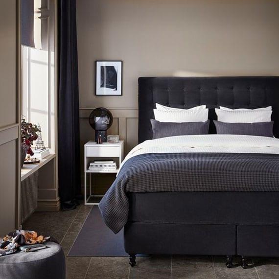 kleines schlafzimmer mit fliesenbodenbelag einrichten im klassischen stil mit hochwertigem boxspringbett und vorhängen in dunkellgrau, modernen nachttischen weiß und wandfarbe beige