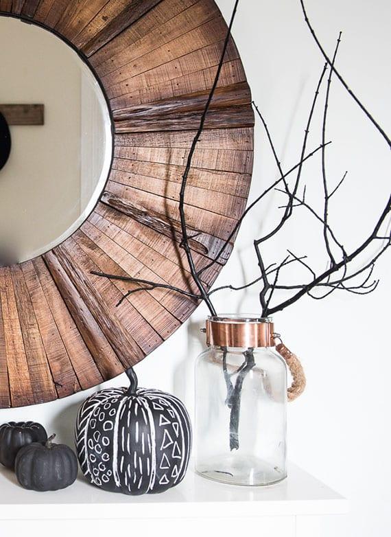 moderne hebstdeko für sideboards mit rundem spigel im attraktiven holzrahmen, zweig in glasvase und schwarzen kürbissen