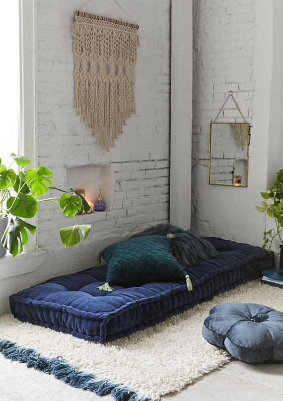 attraktive zimmergestaltung im boho stil mit weißen ziegelwänden, gemütliche sitzke mit matratzenkissen auf teppich und dekokissen in dunkelblau, wanddeko mit spigel und karamee