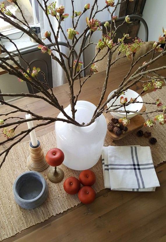 rustikale tischdekoration mit blühenden zweigen in weißer Vase, roten öpfeln und mini-zapfen