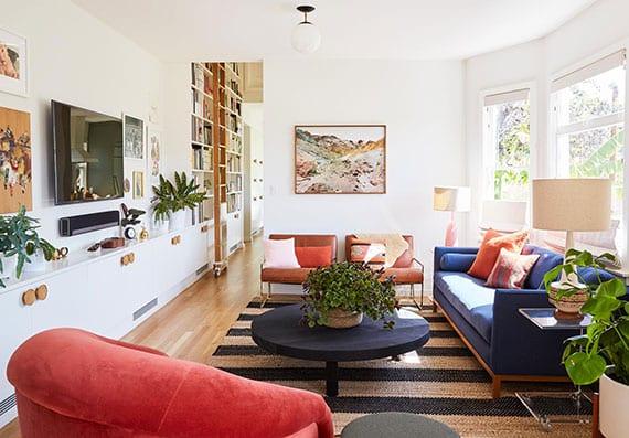 coole wohnzimmer idee für bunte innengestaltung mit sofa in blau, rotem sessel, rundem holzcouchtisch schwarz und fernsehwand aus weißen schränken