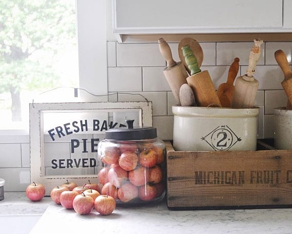 kreative küchendeko idee im rustikalen stil mit roten öpfeln im glas, diy holzfenster-schild und vielen holzteigroller