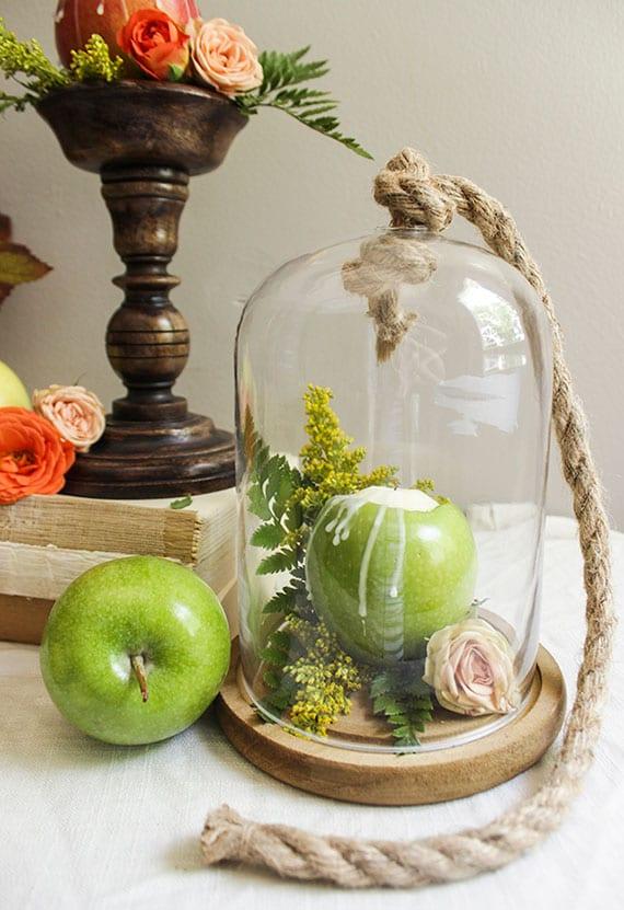 reizvolle tischdekoration mit rosen, grünen äpfeln und farn unter einer glasglocke