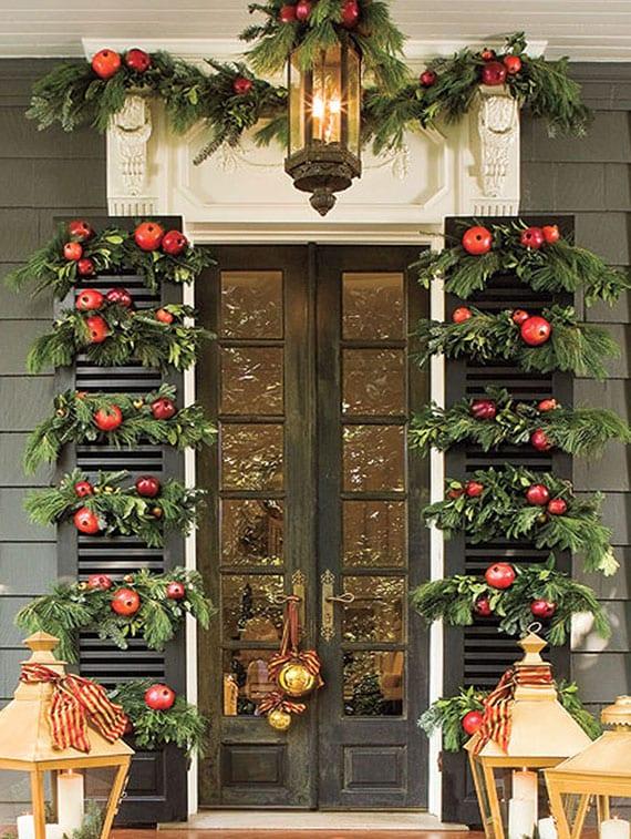 frühliche türdekoration zu weihnachten mit immergrünen zweigen und roten äpfeln