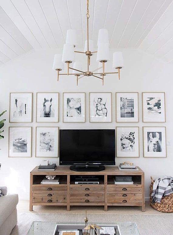 gemütliches wohnzimmer design in weiß mit holzdeckenverkleidung, vintage-TV-Schrank aus holz, elegante wanddeko mit schwarzweißen fotografien und klassischem kronleuchter