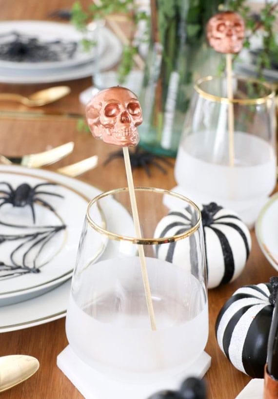 coole tischdeko idee zu halloween mit mini-kürbissen in schwarzweißem streifenmuster, platzteller deko mit spinnen und spinnengewebe und diy Totenkopf-Getränkerührstäbchen