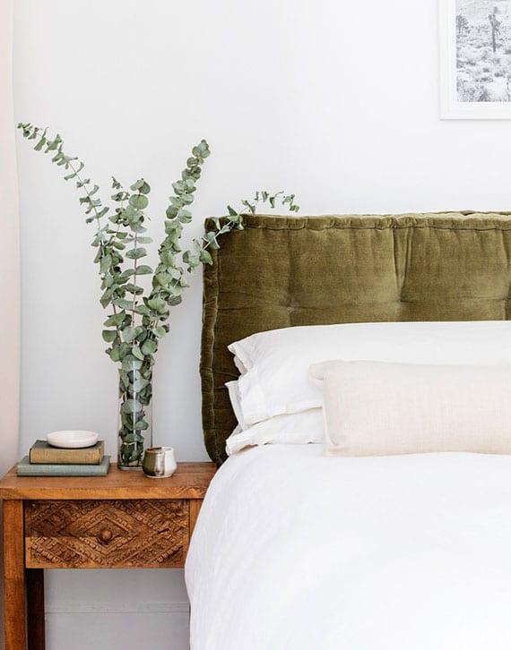 rustikale schlafzimmergestaltung mit holznachttischen und diy bettlehne aus grünen bodenkissen