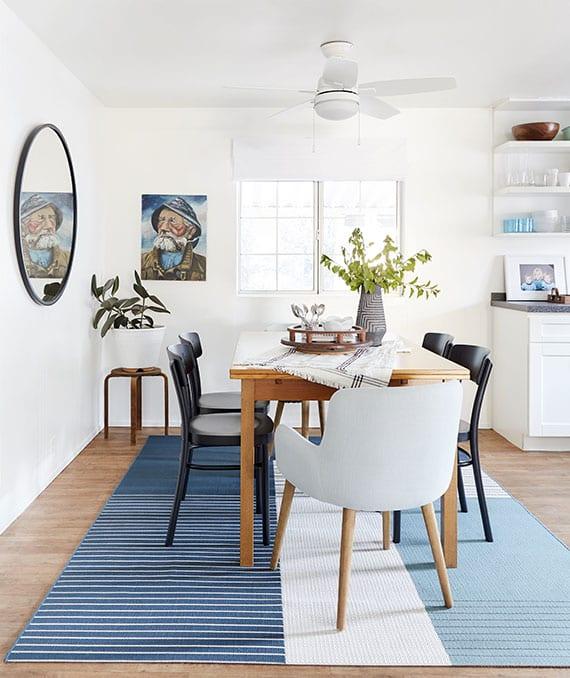 essplatz im wohnzimmer einrichten als essgruppe mit schwarzen holzstühlen und weißen armsesseln um einen holzesstisch auf teppich blau
