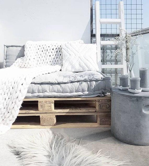 coole einrichtungsidee für kleine terrassen und balkons mit rundem beistelltisch aus beton, diy palettensofa mit grauem sitzkissen und weißer strickdecke, holzleiter und kerzen als stilvolle deko