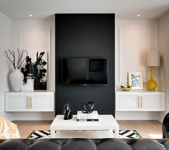 kleines wohnzimmer elegant und stimmungsvoll gestalten mit einer akzentwand für TV, ledersofa schwarz mit weißem couchtisch und zwei wandschränken als kleine sideboards für deko