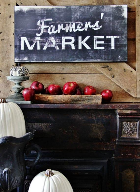ideen für eine herbstliche Kamindekoration im Farmhaus-Wohnstil mit weißen Kürbissen und roten Äpfeln in einer Holzschale