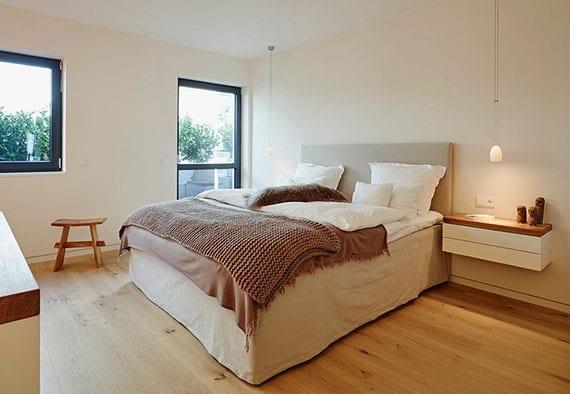 elegante schlafzimmeridee mit hellem interieur in holz und weiß mit doppel-boxspringbett, hängeleuchten über wand-nachttischen mit schubladen und schwarzen fensterrahmen