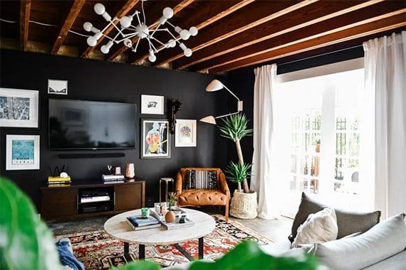stilvolle wohnzimmergestaltung mit holzbalkendecke, scharzer akzentwand hinter TV mit bilderdeko und designer wandlampe, kuscheligem ecksofa mit rundem couchtisch holz auf türkischem teppich