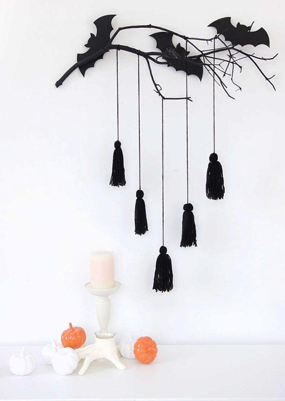 kreative und einfache DIY wandeko zu halloween mit einem zweig, quasten und papier-fledermäusen