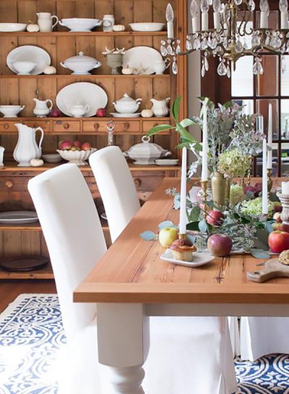 esszimmer im herbstzaumer dekorieren mit roten äpfeln, weißem porzellangeschirr, kerzen und eukalyptus