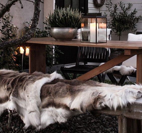 coole und romantische gartengestaltung mit pelzüberwurf auf gartenbank und holzstühlen, Heide in metall-pflanzenkübel, kerze in moderner laterne schwarz