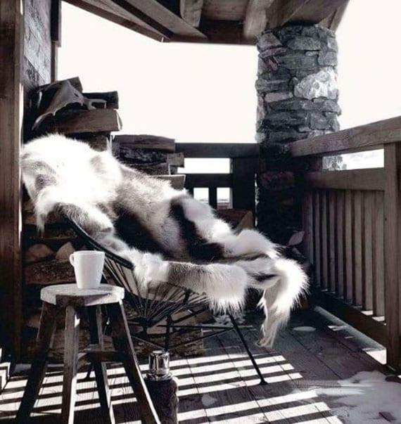 balkon und terrasse rustikal und gemütlich für den winter einrichten mit feuerholz, sessel mit pelz und holzhocker als kleiner beistelltisch