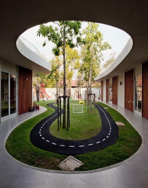 abenteuerlicher spielplatz für kinder im garten gestalten mit einer mini-rennbahn zwischen bäumen