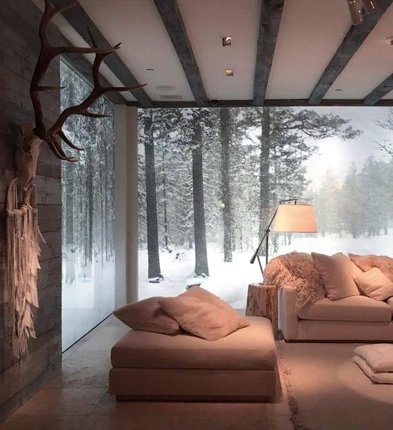 minimalistisches wohnzimmer design mit wänden aus sichtbeton,eckfenster mit panoramblick, modernen seats and sofa in weiß, tischlampe auf stumps-beistelltisch und wanddeko mit traumfänger und geweih