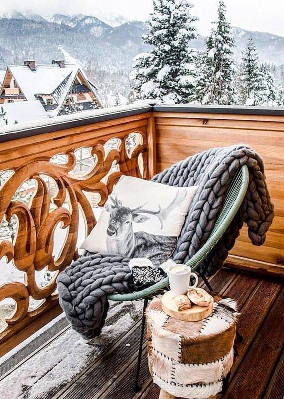 balkon im winter schön und gemütlich einrichten mit hocker aus pelz, sessel mit dicker strckdecke grau und dekokissen mit hirschmotiv