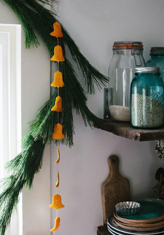 fenster weihnachtlich dekorierenmit tannengrün und diy girlande mit glocken aus orangenschale